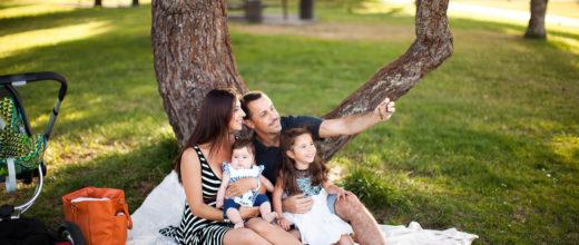 Eine Frau und ein Mann sitzen mit Kindern vor einem baum in einem Park. Der Vater zeigt auf etwas in der Luft und das ältere Kind schaut gespannt in diese Richtung. die Frau sieht seitlich zu dem Mann.