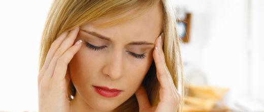 Junge blondhaarige Frau die sich aufgrund von Kopfschmerzen mit beiden Händen an die Schläfen packt