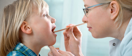 Eine Ärztin schaut in den Rachen eines kleinen Jungens