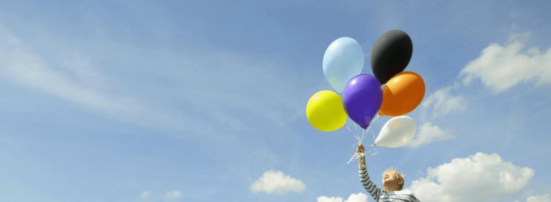 Auf einer Wiese sieht man einen Jungen der mit sechs verschieden farbigen Ballons über dem Boden zu schweben scheint