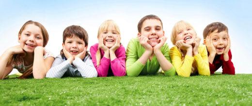 Sech Kinder liegen auf einer Wiese und stützen sich den Kopf auf ihren Händen ab. Es sind drei Jungs und drei Mädchen, immer abwechselnd.