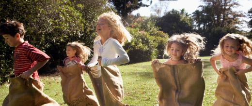 Fünf Kinder die in Hüpfsäcken über eine Wiese hüpfen