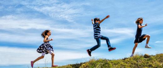 Drei Kinder springen fröhlich auf einem Hügel, man sieht diesen nicht ganz da er abgeschnitten ist. Es sind zwei Mädchen und ein Junge. Das eine Mädchen trägt ein dunkelblaues Kleid mit weißen Blumen darunter eine weiße Radlerhose, der Junge trägt Jeans, Turnschuhe und ein gestreiftes Polohemd, das andere Mädchen ein dunkelblaues Kleid mit weißen Sneakern