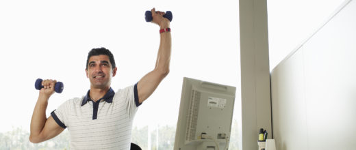 Mann am Pc bzw Schreibtisch mit kleinen hanteln in der Hand, linker Arm nach oben gestreckt