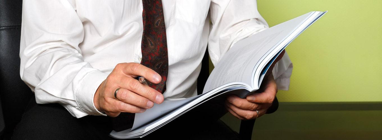 Mann hält eine Mappe sowie einen Stift in der hand und blättert durch die Seiten der Mappe