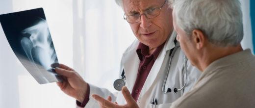 Arzt hält ein Töntgenbild von der Schulter, ein älterer Mann steht neben ihm und sieht auf die Röntgenaufnahme