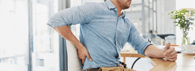 Mann mit blauem Hemd und brauner Hose sitz an einem Schreibtisch und hält sich Schmerzverzerrt den Rücken