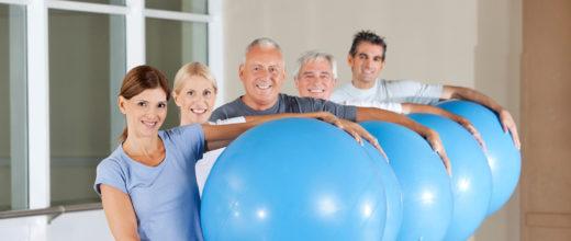 Fünf Personen mittleren alters stehen leciht versetzt in einer Reihe hintereinander und halten dabei jeweils einen blauen Medizinball