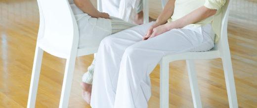 Personen sitzen sich auf Stühlen die nebeneinander stehen gegenüber. Sie tragen Helle Kleidung. Die Stühle sind weiß.