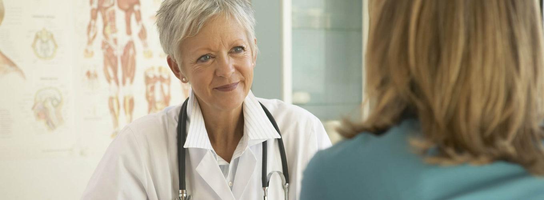 Eine Ärztin sitzt einer Patientin im Behandlungsraum gegenüber