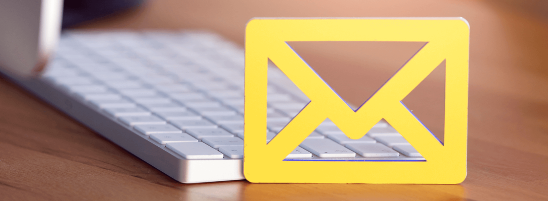 Ein gelbes Briefsymbol das vor einer weißen Tastatur steht