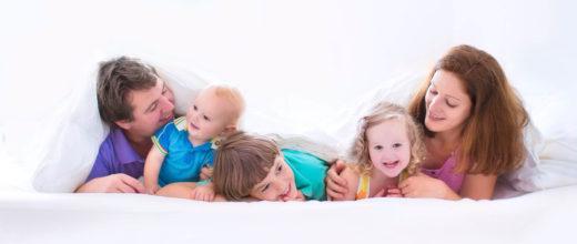 Familie liegt im Bett mit Kindern, der Hintergrund und alles herum ist weiß gehalten