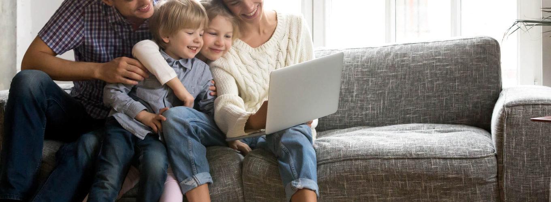 Familie auf Couch, Frau, Mann und zwei Kinder mit einem Laptop auf dem schoß
