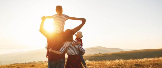 Familie bei Sonnenuntergang auf einem Feld, Vater hat Kind auf den Schultern, Mutter ein Kind auf dem Arm