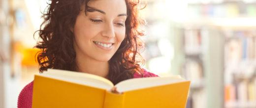 Eine dunkelhaarige Frau die ein aufgeschlagenes orangefarbendes Buch in der Hand hält