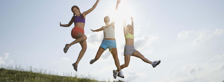drei Frauen springen auf einem Hügel nach obenm im Hintergrund scheint die Sonne