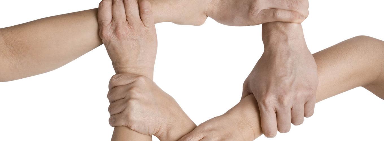 Leute halten sich im Kreis am Handgelenk fest
