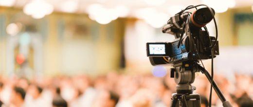 Eine Kamera steht auf einem Stativ vor einem großem Publikum welches im Hintergrund verschwommen ist.