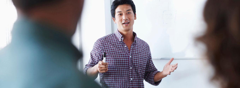ein Mann erklärt anderen Leuten etwas am Whiteboard