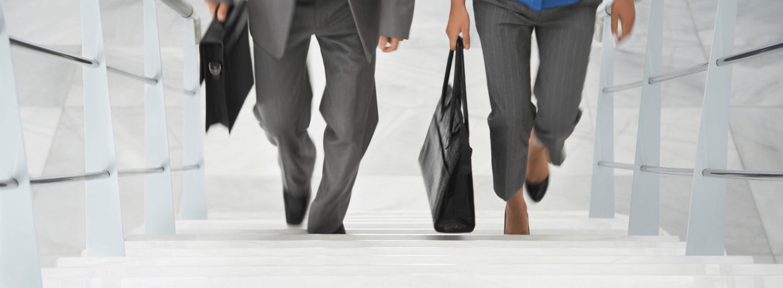 Ein Mann und eine Frau mit jeweils einer schwarzen Tasche in der hand gehen gemeinsam eine Treppe hinauf