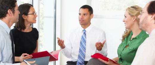 Mehrere Personen halten ein Meeting ab (zwei Frauen und drei Männer)