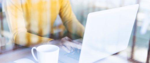 Eine Person mit gelben Pullover sitzt mit einer Tasse an ihrem Laptop.