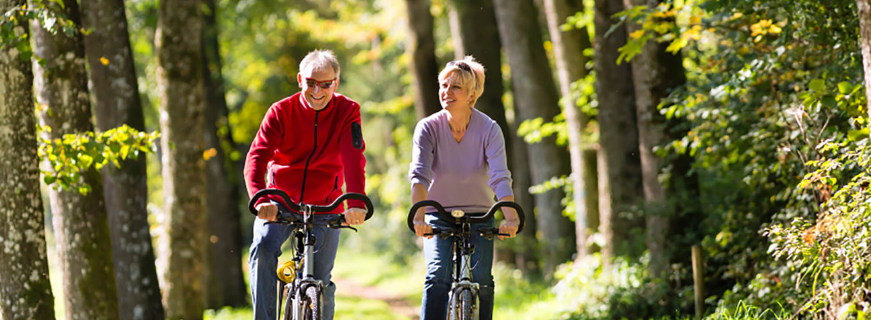 alte Leute im Wald fahren Fahrrad